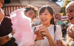 Young people eating cotton candy at a festival