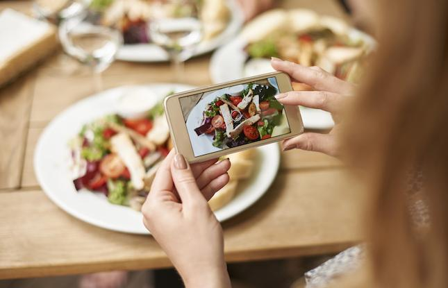Girl taking a picture of her food