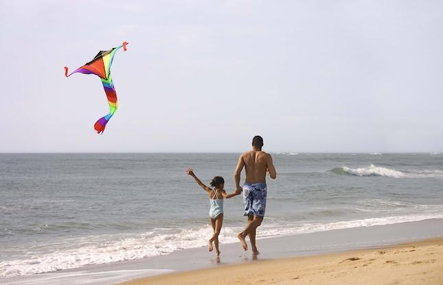 Dad and Daughter flying kite on the beach