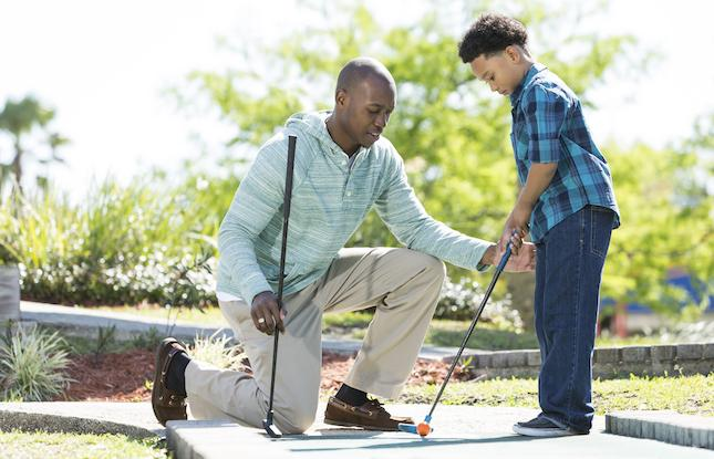 father and son mini-golfing