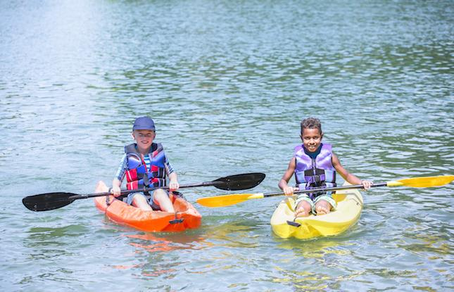 Diverse children in kayaks on lake