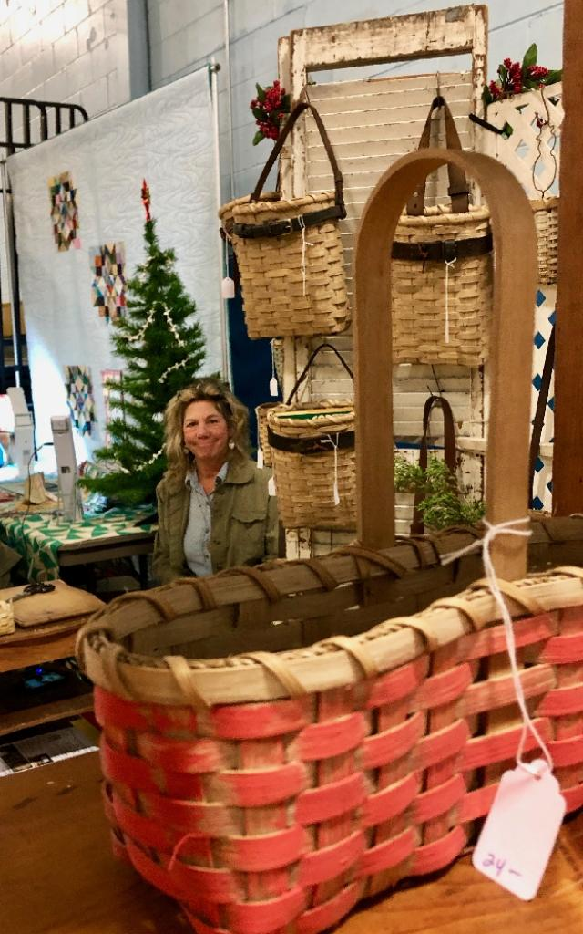 Patti from Riverbend Baskets continues making baskets during the show between customers.